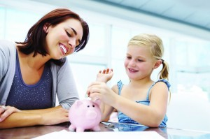 Brown haired woman and blond girl smile as girl drops money in piggy bank.
